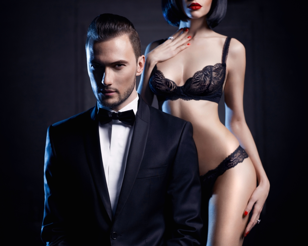 Fashion studio photo of a sensual couple in lingerie and a tuxedo